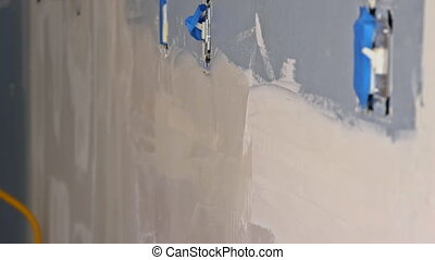 Closeup of a man aligning a wall with spatula and plastering gypsum cardboard wall