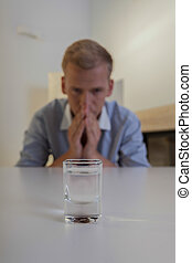 Man and a glass of vodka on the table