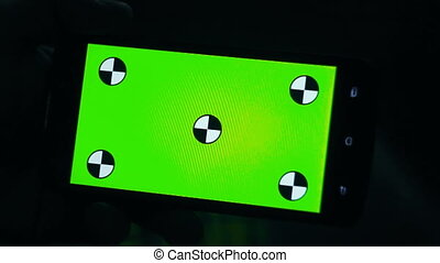 man and a green screen smartphone