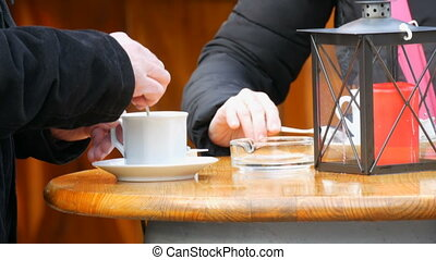 Man and a woman are drinking coffee in a street cafe. A man...