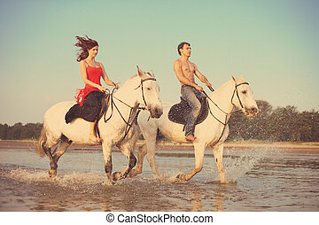 Man and a woman in love with the sea on horseback