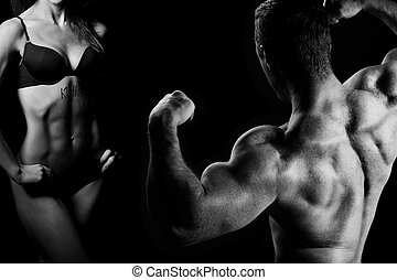 man and a woman in the gym - Bodybuilding. Strong man and a ...