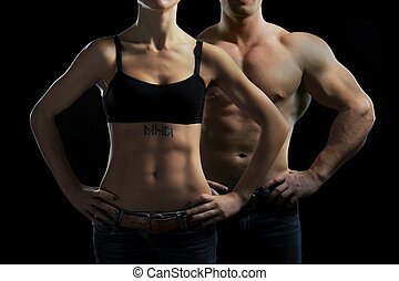man and a woman in the gym - Bodybuilding. Strong man and a...
