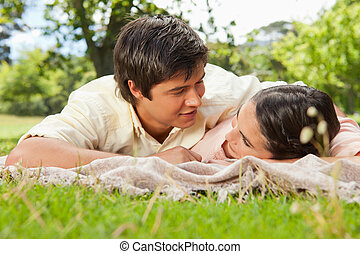 Man and a woman looking into each others eyes while lying prone on a grey blanket in the grass