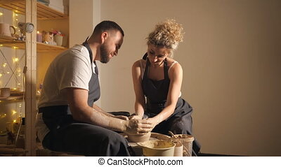 man and a woman making clay jug on potter's wheel. romantic...