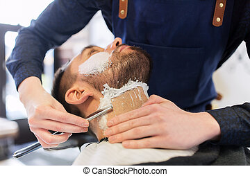 man and barber with straight razor shaving beard - grooming...