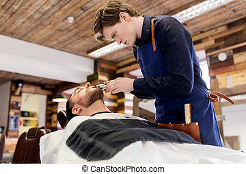 man and barber with trimmer cutting beard at salon