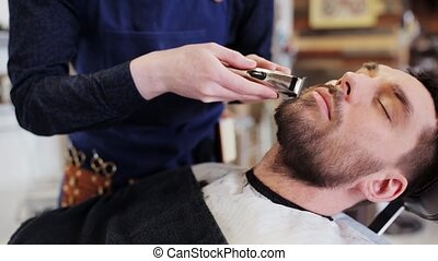 man and barber with trimmer trimming beard at shop