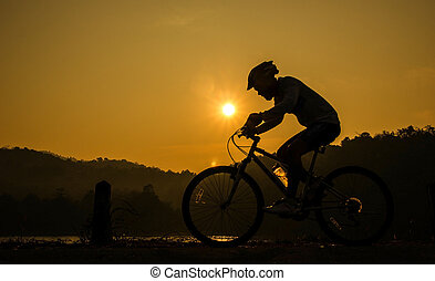 Man and bike silhouette with the sky as background.