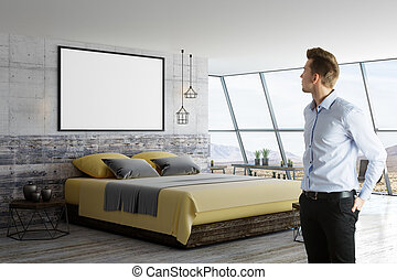 man and blank poster in loft room