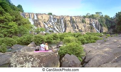 man and blond woman sit backside on mat among landscape