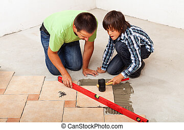 Man and boy laying ceramic floor tiles