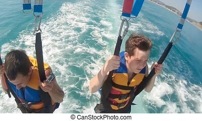 man and boy paragliding and lifestyle parasailing. are flying on a parachute over the sea. Extreme sport first-person view
