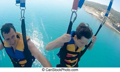 man and boy paragliding and parasailing. are flying on a...