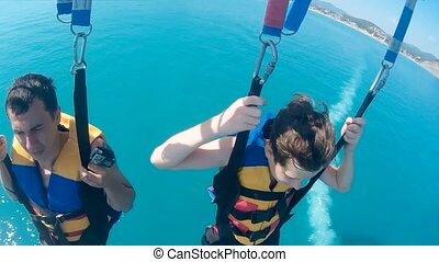 man and boy paragliding and parasailing. lifestyle are...