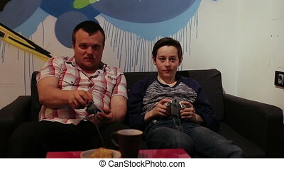 Man and boy Playing in Computer Game with Joystick -...