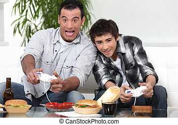 man and boy playing to video games