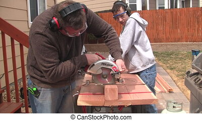 Man and boy sawing wood