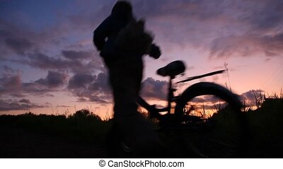 man and boy with bicycles looks at sunset