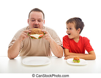 Man and boy with hamburgers - teaching healthy or unhealthy...