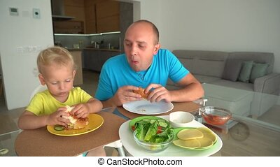 Man and boy with hamburgers - teaching healthy or unhealthy diet by example concept. Gimbal camera motion shot.
