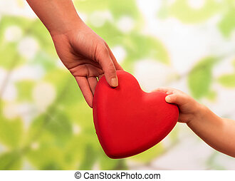 Man and child hands holding heart on green background