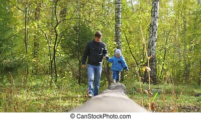 Man and child walking in the Park on a fallen tree