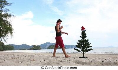 man and Christmas tree on the beach