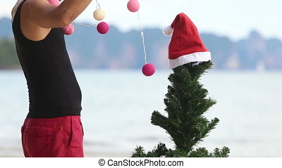 man and Christmas tree on the beach - guy decorates a...