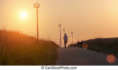 A man and a dog at a wheat field with sundown and wind turbine