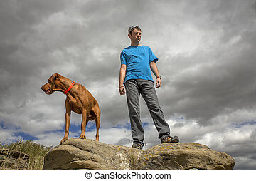 man and dog on top of cliff