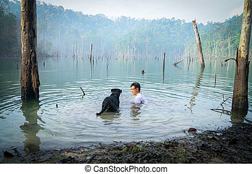 Man and dog playing and swimming in a lake.