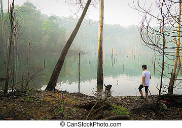 Man and dog spending time together at a misty lake