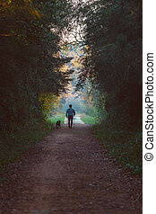 Man and dog walking in a natural tunnel