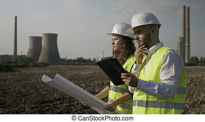 Man and female engineers coworkers analyzing and checking scheme project plans near gas energy factory