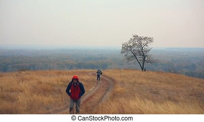 man and female man woman  tourists are on road lonely tree nature autumn tour travel