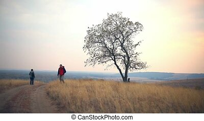 man and female man woman  tourists are on way road lonely tree nature autumn tour travel
