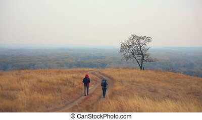 man and female tourists are on road lonely tree nature autumn tour travel