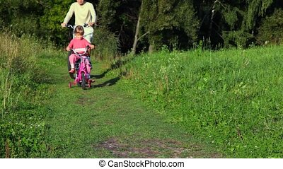 man and girl riding bicycles in park
