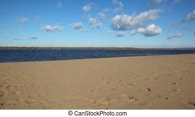 man and girl runs on sandy beach