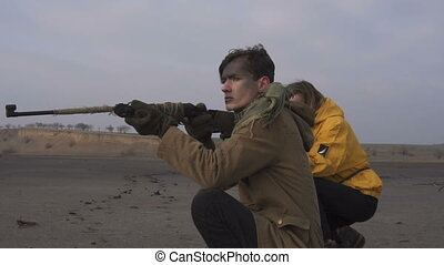 Man and Girl take aim in cloudy wasteland. Stalker - Survival concept. Couple with firearms weapons. Girl with shotgun and Guy with rifle.