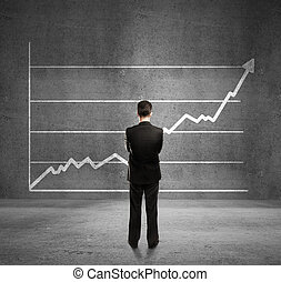 man and growth chart - businessman looks at growth chart
