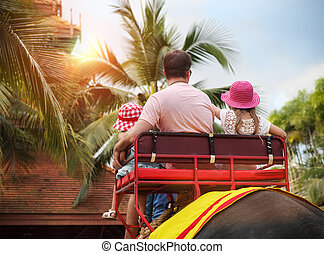 Man and his daughters riding on the back of elephant