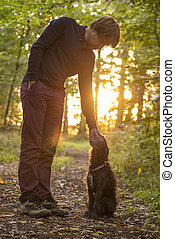 Man and his dog enjoying nature as he stands bending down to...