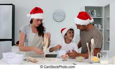 Man and his family cooking christmas cookies in the kitchen