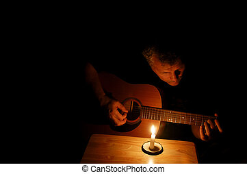 Man and His Guitar - A middle-aged man playing his guitar at...