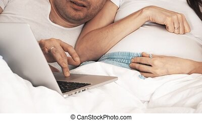 Man and his pregnant wife shopping online at home - Man and...