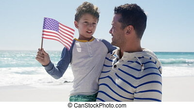 Man and his son enjoying free time on the beach together - ...