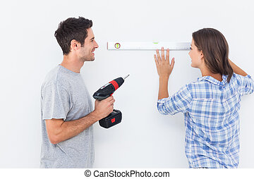 Man and his wife doing diy together with a drill and a...
