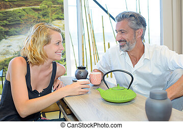 Man and lady enjoying a hot drink together